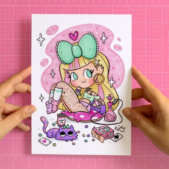 manos sosteniendo una lámina impresa con una ilustración kawaii