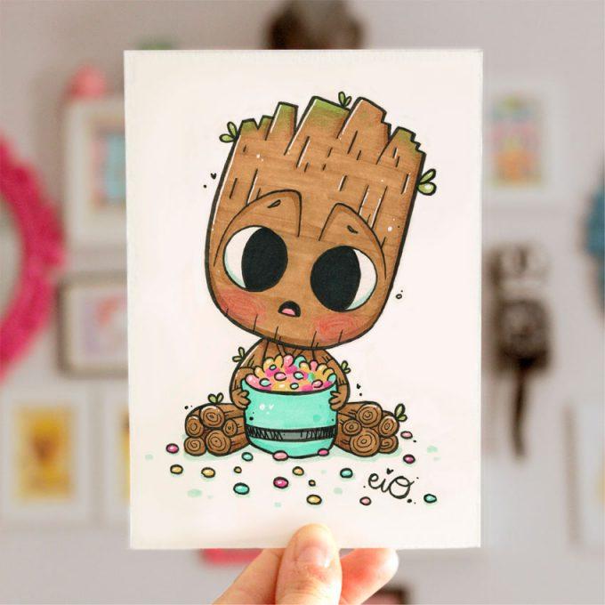 mano cogiendo una lamina impresa ilustrada con un dibujo de Baby Groot