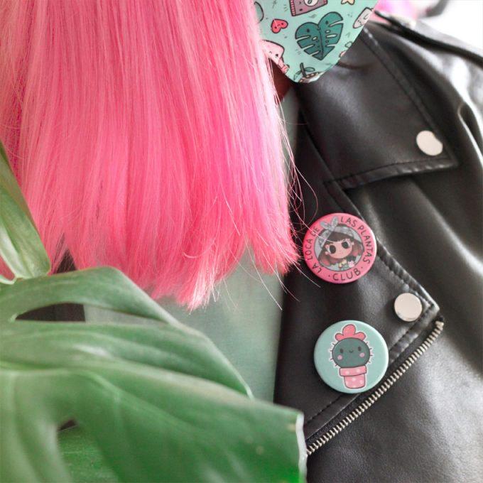 chica con pelo rosa llevando chapas ilustradas con plantas sobre chaqueta negra