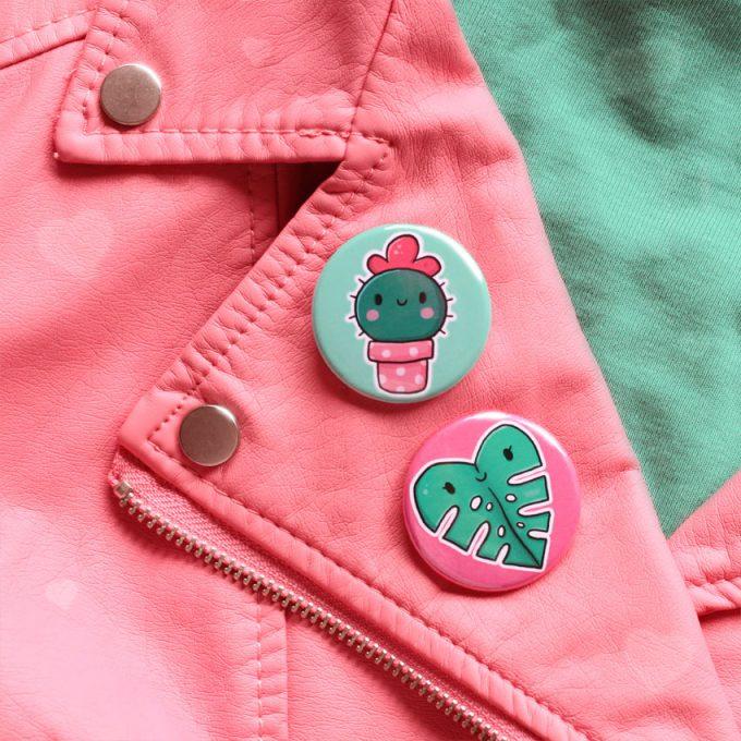 chapas ilustradas con catus y monstera sobre chaqueta rosa