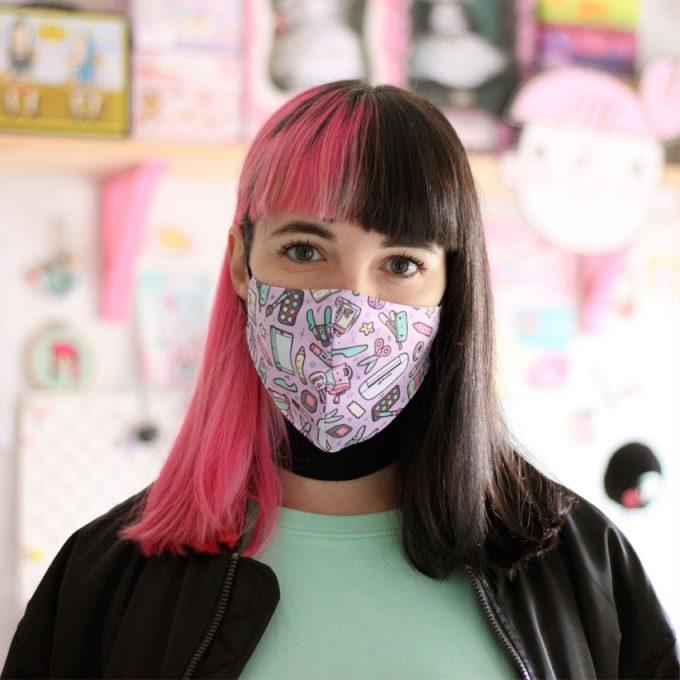 chica con pelo rosa y negro llevando una mascarilla con ilustraciones de Scrap